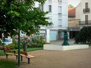 Néris-les-Bains - Fountain, benches, flowerbeds and facades of the spa town