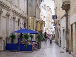 Nîmes - Alleyway in the old town: cafe terrace, shops and facades of houses
