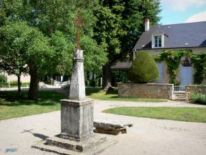 Nohant - Calvary (cross) on the church square and houses of the village; in the town of Nohant-Vic