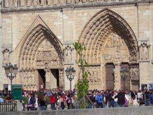 Notre-Dame de Paris cathedral - Portals of the west facade and visitors in the cathedral esplanade