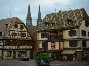 Obernai - House with glazed tiles on the roof, half-timbered residence and Saints-Pierre-et-Paul church in background