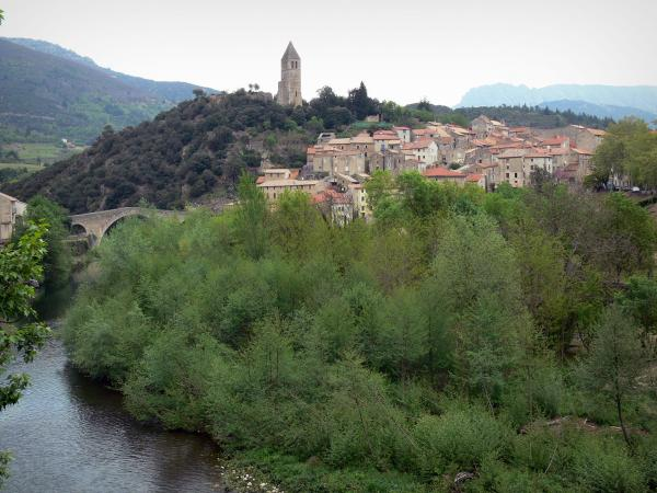 Olargues - Bell tower dominating the houses of the village, bridge on the River Jaur and trees along the water, hills in background, in the Upper Languedoc Regional Nature Park