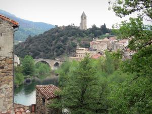 Olargues - Stone house in foreground with view of the bell tower, houses of the village, bridge on the river and trees along the water, in the Upper Languedoc Regional Nature Park