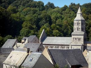 Orcival basilica - Octagonal belfry of the Romanesque Basilica Notre-Dame, roofs of houses and trees; in the Auvergne Volcanic Regional Nature Park, in the Monts Dore mountain area