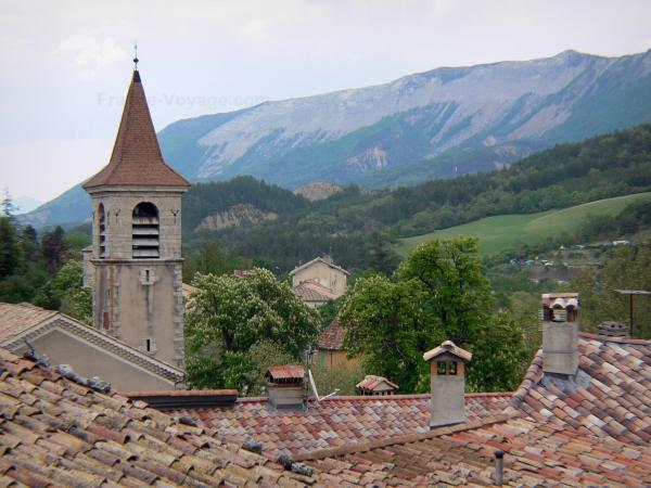 Orpierre - Church bell tower and roofs of the houses in the village with view of the mountain