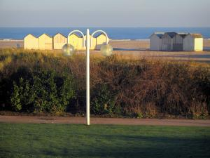Ouistreham - Alley with a lamppost, lawn, bushes, beach huts and the Channel (sea) in background