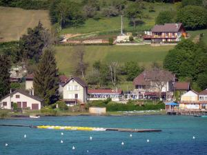 Paladru lake - Natural lake of glacial origin, moored paddle boats, bank, houses, fields and trees