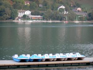 Paladru lake - Pedal boats on a pontoon, natural lake of glacial origin and sailing school in the background