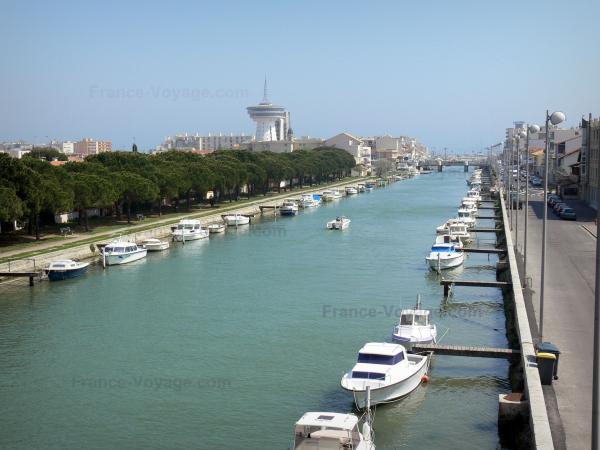 Palavas-les-Flots - Seaside resort: canal, moored boats, quays, trees, houses, buildings and lighthouse of the Mediterranean Sea