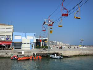 Palavas-les-Flots - Cable car, canal, moored boats, café terrace, houses and buildings of the seaside resort