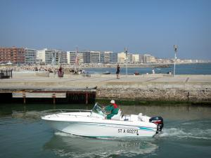 Palavas-les-Flots - Boat navigating the canal, promenade, beach, Mediterranean Sea, houses and buildings of the seaside resort
