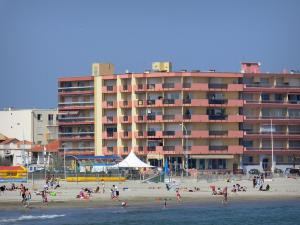 Palavas-les-Flots - Sandy beach with holidaymakers, playground, Mediterranean Sea, houses and buildings of the seaside resort