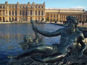 Park of the Palace of Versailles - Statue in foreground, waterbed pond (parterre d'Eau) and castle