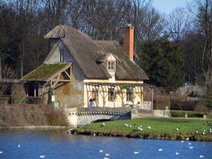 Park of the Palace of Versailles - Queen's hamlet: Grand lake and house with a thatched roof