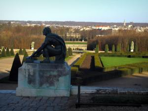 Park of the Palace of Versailles - Statue in foreground with view of gardens