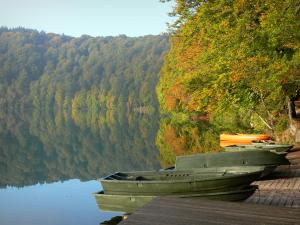 Pavin lake - Small boats on the lake and trees (forest) with autumn colours reflecting in the water; in the Auvergne Volcanic Regional Nature Park, in the Massif du Sancy mountains (Monts Dore), near Besse-et-Saint - Anastaise