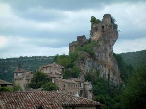 Penne - Roof of a house in foreground and ruins of the castle (fortress) perched on a rocky mountain spur and overhanging the houses of the village (Albigensian fortified town), trees and forest, cloudy sky