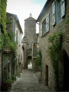 Penne - Narrow street lined with stone houses and view of the Pont gateway