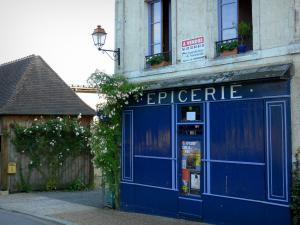 La Perrière - Front of the grocery store and climbing rosebushes in bloom