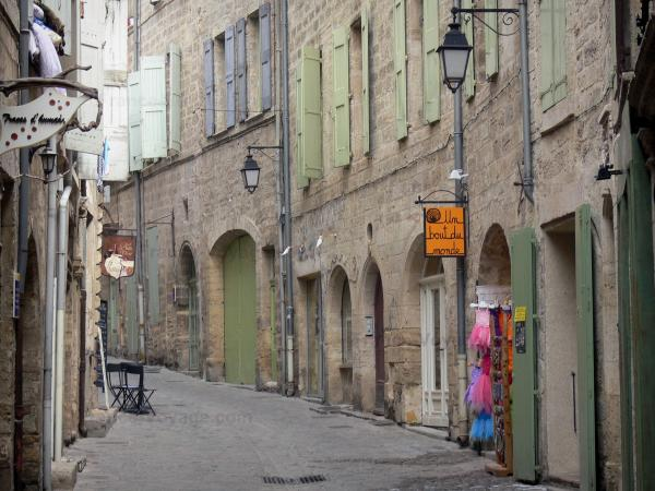 Pézenas - Old town: narrow paved street lined with shops and stone houses with green shutters