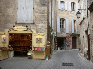 Pézenas - Old town: narrow paved street, workshops, stone houses