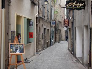 Pézenas - Old town: easel, narrow paved street lined with workshops and houses