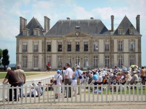 Le Pin national stud farm - Facade of the château, horse rider and spectators of Jeudis du Pin equestrian show; in the town of Le Pin-au-Haras