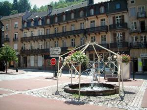 Plombières-les-Bains - Square decorated with a pond and a fountain, houses of the hydropathic city (resort) in background