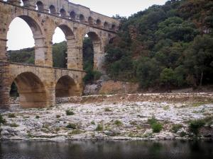 Pont du Gard bridge - Roman aqueduct (ancient monument) with three levels of arcades (arches), bank lined with trees and River Gardon; in the town of Vers-Pont-du-Gard