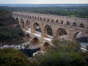 Pont du Gard bridge - Roman aqueduct (ancient monument) with three levels of arcades (arches) spanning the River Gardon and  banks planted with trees; in the town of Vers-Pont-du-Gard