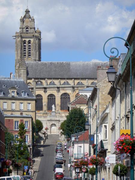 Pontoise - Tower of the Saint-Maclou cathedral and Rue Thiers street lined with houses, lampposts and flowers