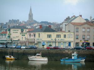 Pornic - Fishing port with its boats and its trawlers moored to the quay, the church and houses of the city (seaside resort)