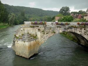 Port-Lesney - Arc of the old bridge decorated with flowers, Loue river, roofs of houses in the village, trees along the water, forest in background
