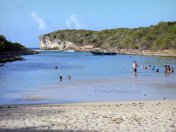 Porte d'Enfer lagoon - Sandy beach, lagoon with swimmers and Porte d'Enfer cliffs; on the island of Grande-Terre