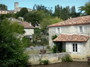 Poudenas - Old mill on the Gélise river, houses of the village, trees and bell tower of the church overlooking the place; in the Pays d'Albret region