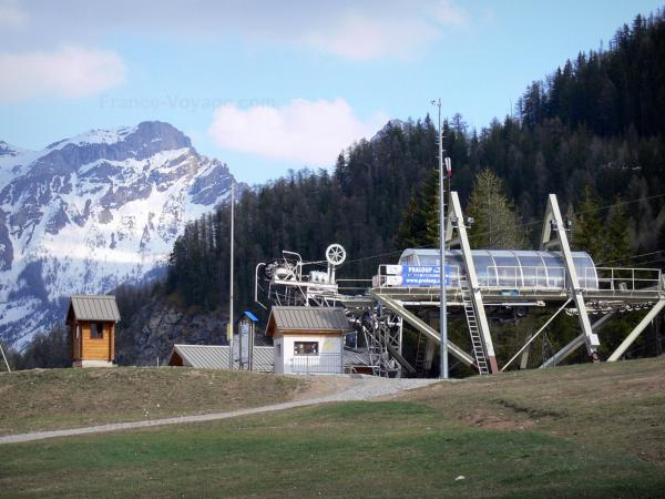 Pra-Loup - Ski lift (chairlift) of the ski resort, trees and mountain