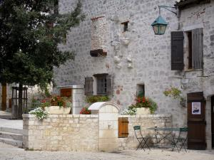 Pujols - Facade of a stone house, tree, flowers, and table with two chairs
