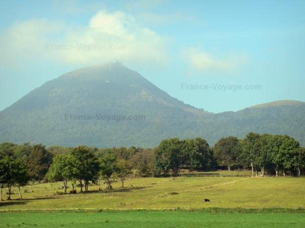 Puy de Dôme volcano - View of the volcano of the Puys mountains (monts Dôme range), its summit and a landscape of trees and meadows downwards; in the Auvergne Volcanic Regional Nature Park