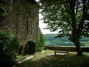 Puycelsi - Stone house and garden featuring a tree and a bench with view of the Grésigne forest