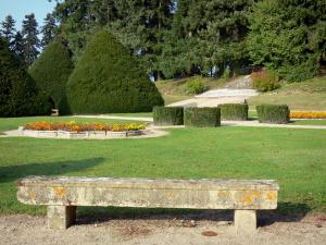 Ravel castle - French-style formal garden of the castle: stone bench, lawns, flowerbeds and yews