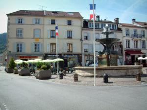 Remiremont - Square with fountain, flags, café terrace, shops and houses of the city