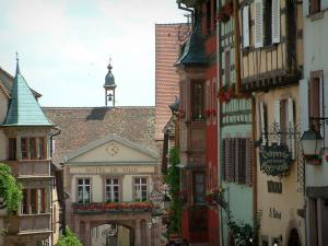 Riquewihr - Houses with colourful facades, oriel windows and forged iron shop signs, building of the town hall in background