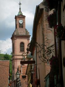 Riquewihr - Houses with colourful facades decorated with forged iron shop signs and the church bell tower in background