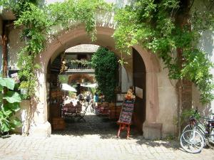 Riquewihr - Small arched passage decorated with creepers leading to a restaurant terrace