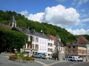 La Roche-Guyon - Fountain and facades of houses in the village and bell tower of the Saint-Samson church overlooking place; clouds in blue sky