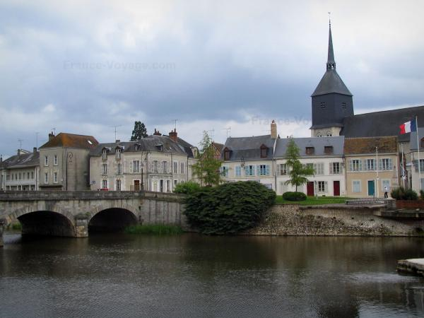 Romorantin-Lanthenay - Saint-Etienne church, houses of the city, bridge spanning the River Sauldre and turbulent sky, in Sologne