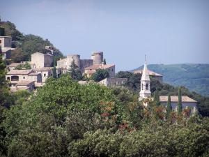 La Roque-sur-Cèze - View of the bell tower of the church and the houses surrounded by trees