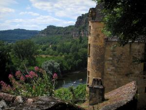 La Roque-Gageac - Roof of a house and a tower of the Tarde manor house with view of the River Dordogne and the trees, the clouds in the sky, in Périgord