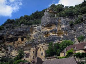 La Roque-Gageac - Houses of the village, the Tarde manor house and troglodyte fort dominating the set, clouds in the blue sky; in the Dordogne valley, in Périgord