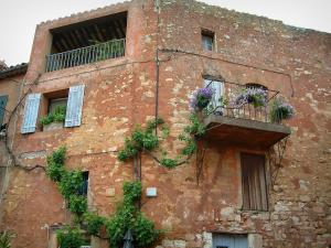 Roussillon - House with red ochre colour and a small balcony, plants and flowers